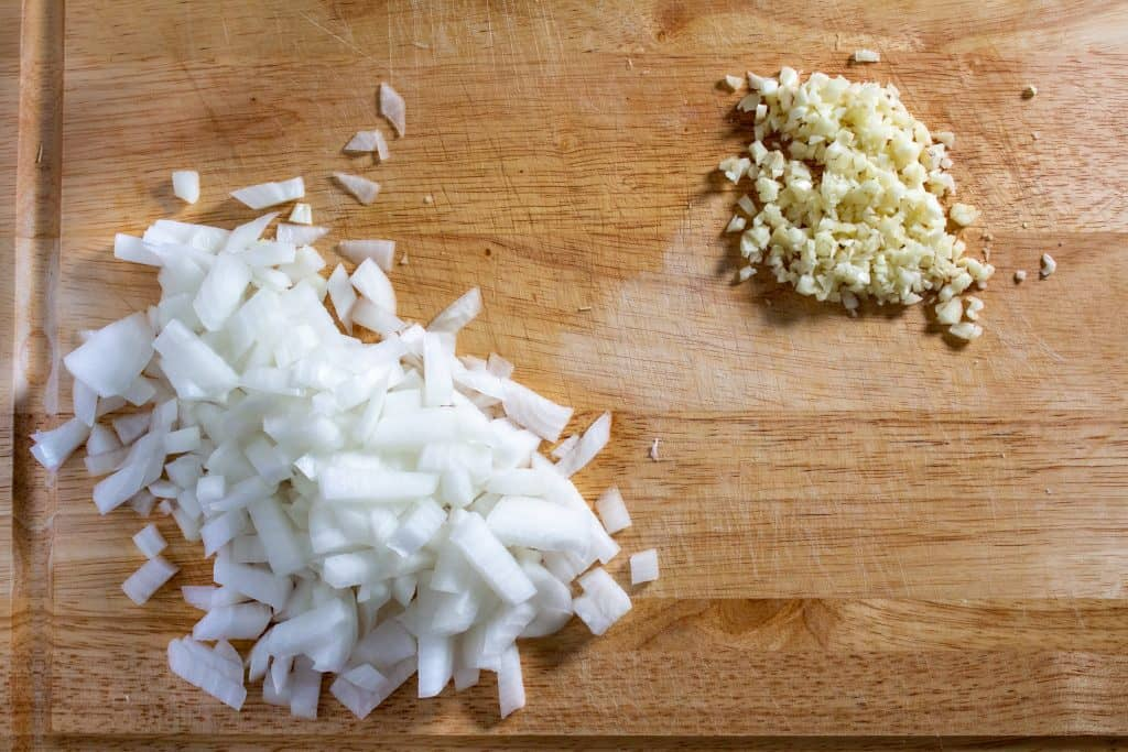 chopped onion and garlic on cutting board