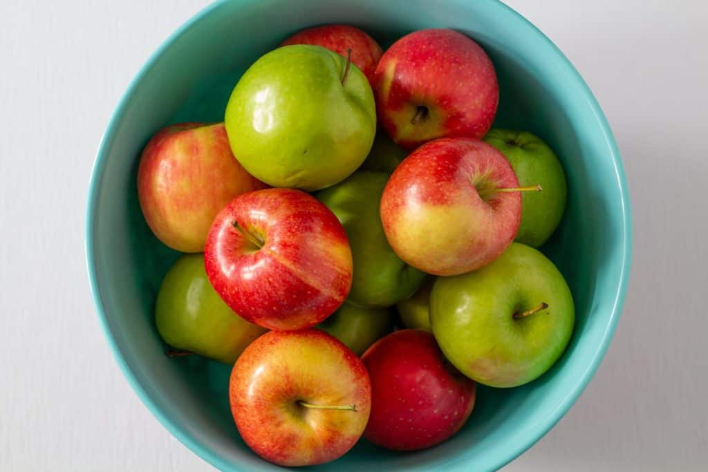 red and green apples in a bowl on a white background