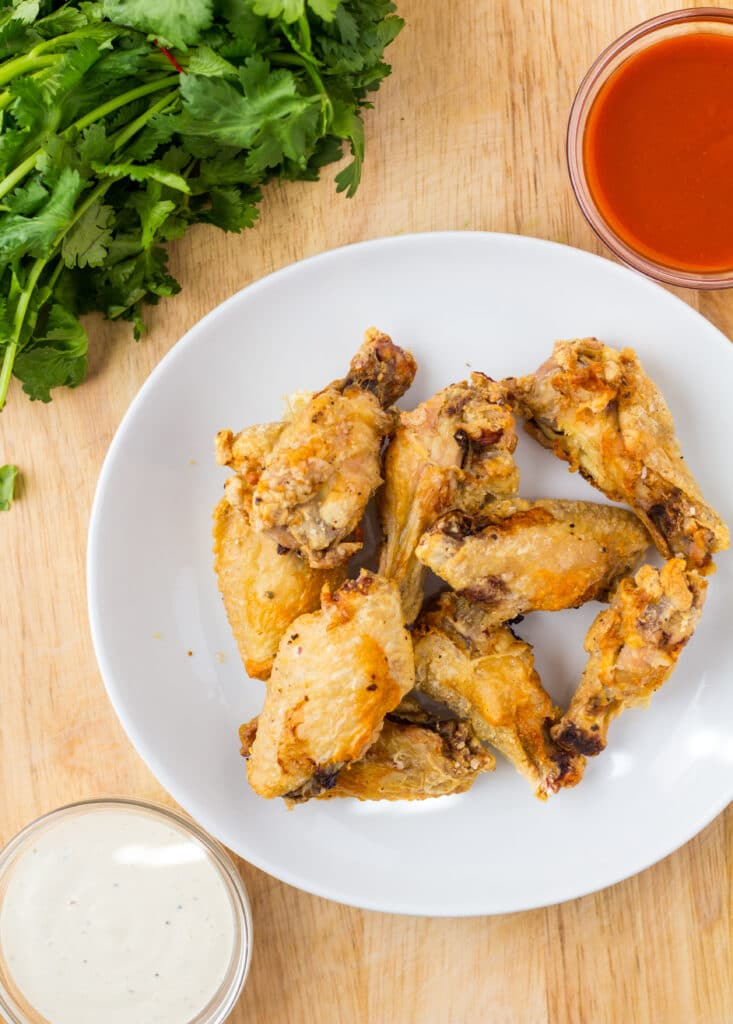 chicken wings on a white plate with sauces