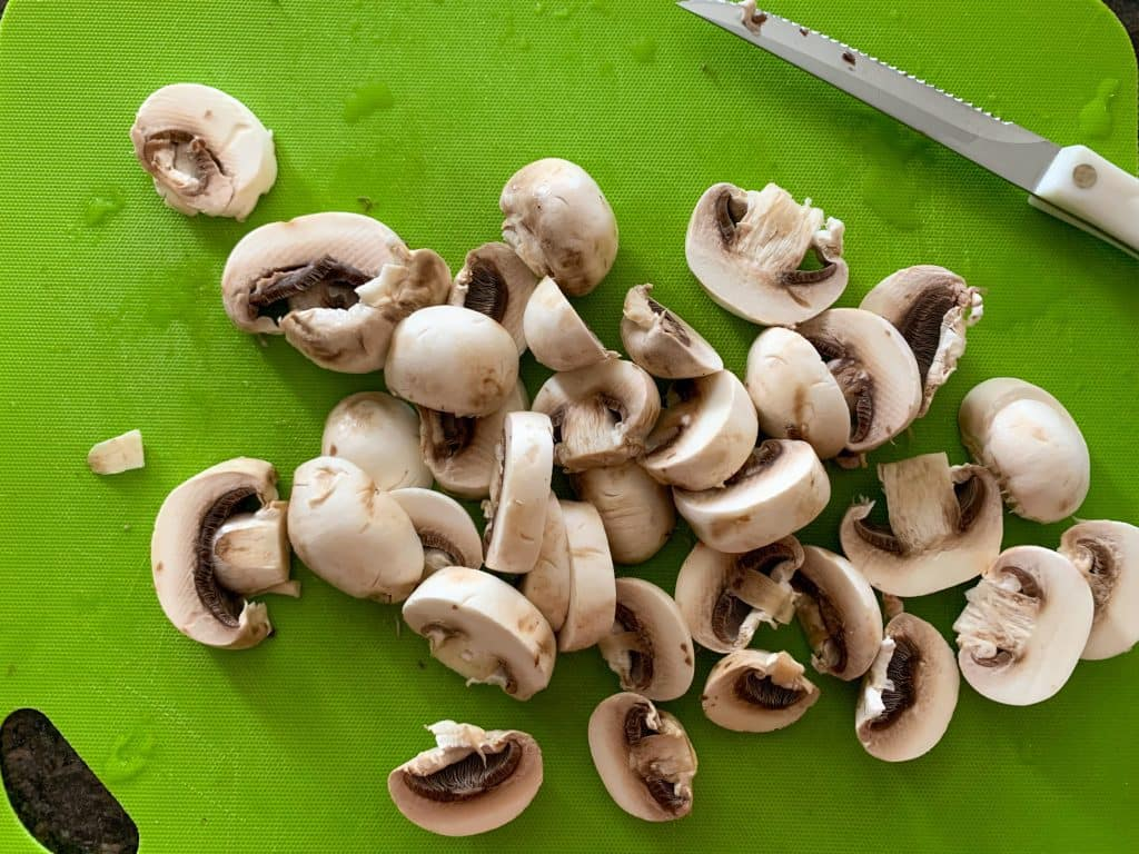 sliced mushrooms on a green cutting board