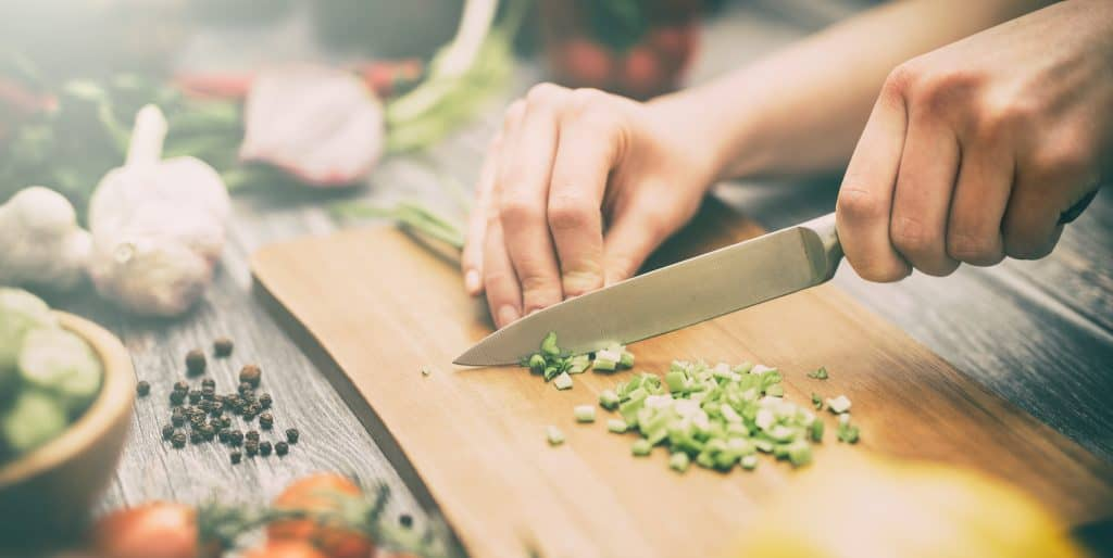 a knife cutting green onions on a cutting board surrounded by vegetables
