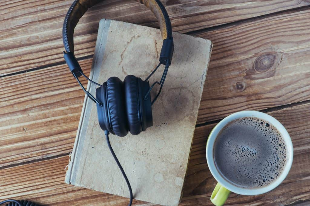 headphones on a book with a cup of coffee sitting on a wooden table