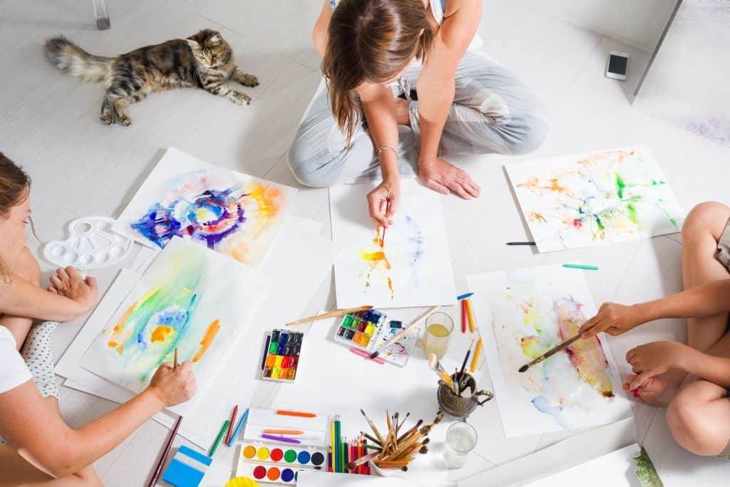 kids painting on a white floor during their time at home