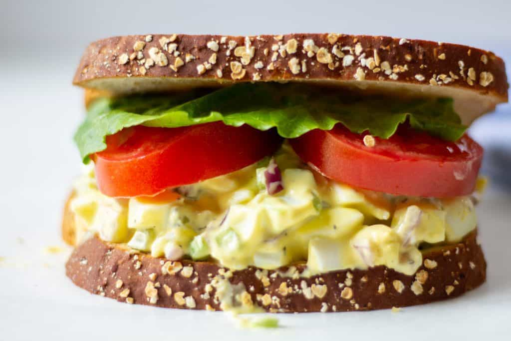 egg salad sandwich with lettuce and tomatoes on a white background